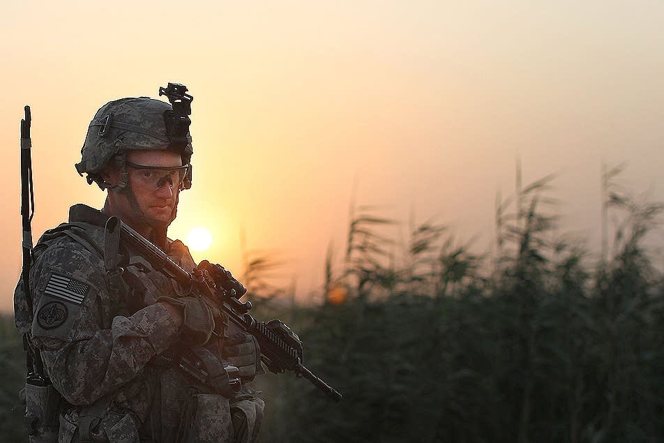 The sun sets behind a U.S. soldier in Iraq