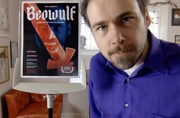 man stares into camera with Beowulf poster behind him