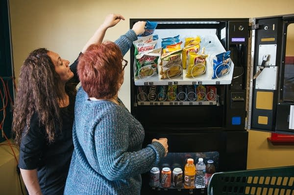 Erica Francis helps Pauline as they restock a vending machine.
