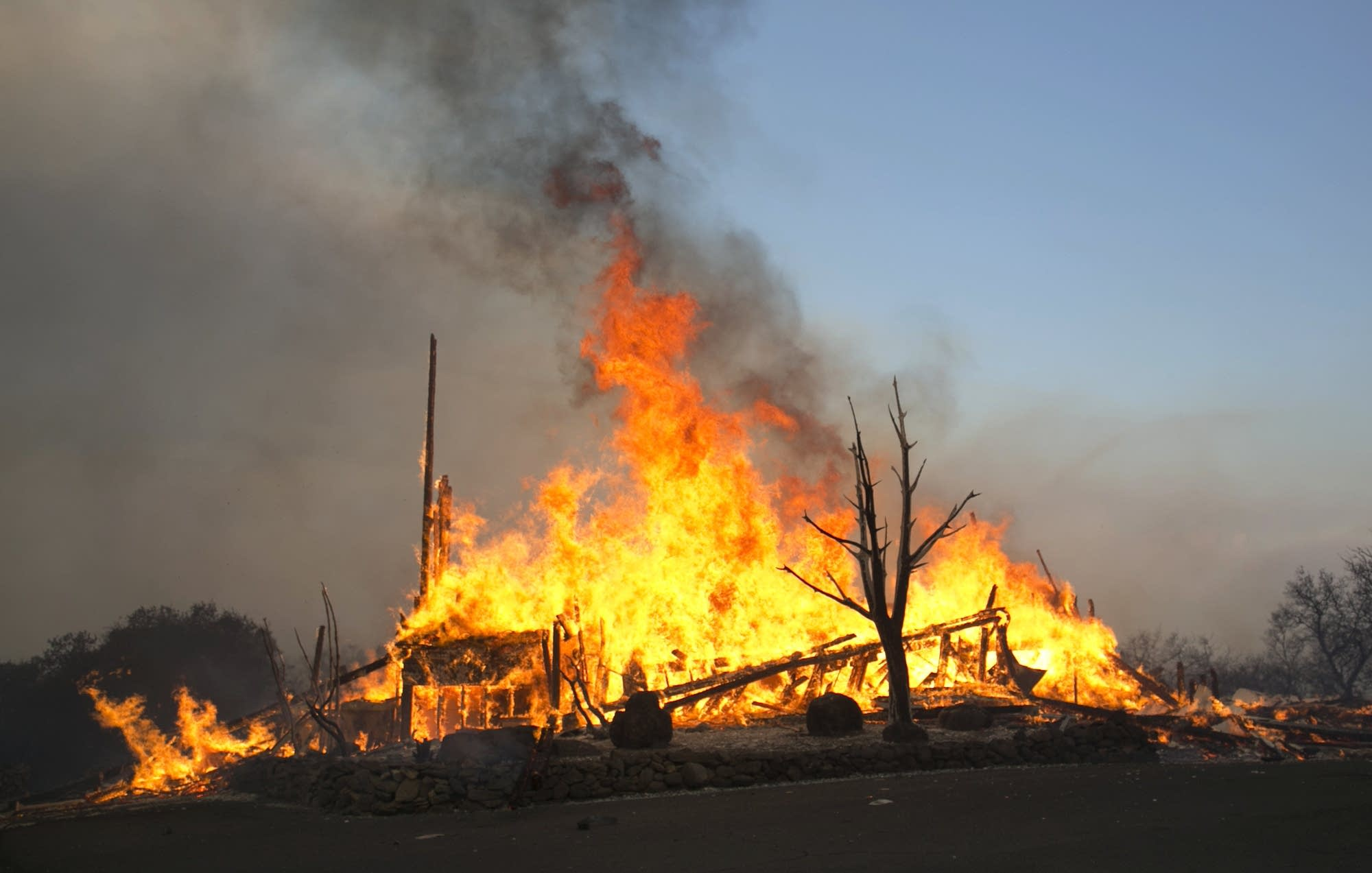 Flames from a wildfire consume a home east of Napa, Calif.