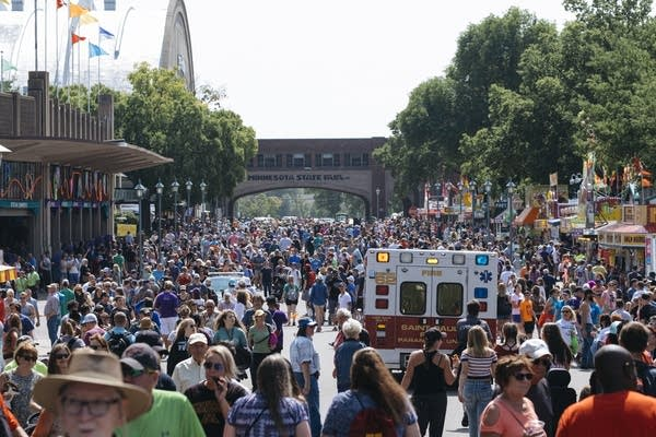 An ambulance cuts through a thick afternoon crowd on Thursday.
