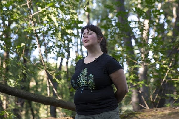 A woman stands in the forest with her eyes closed.