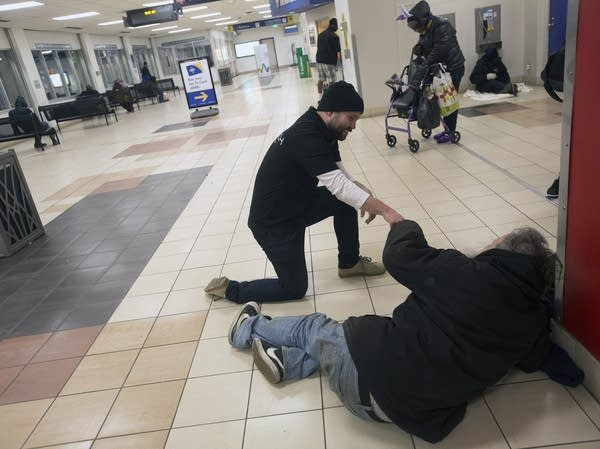Chris Knutson of St. Stephens talks with a homeless man at the LRT.