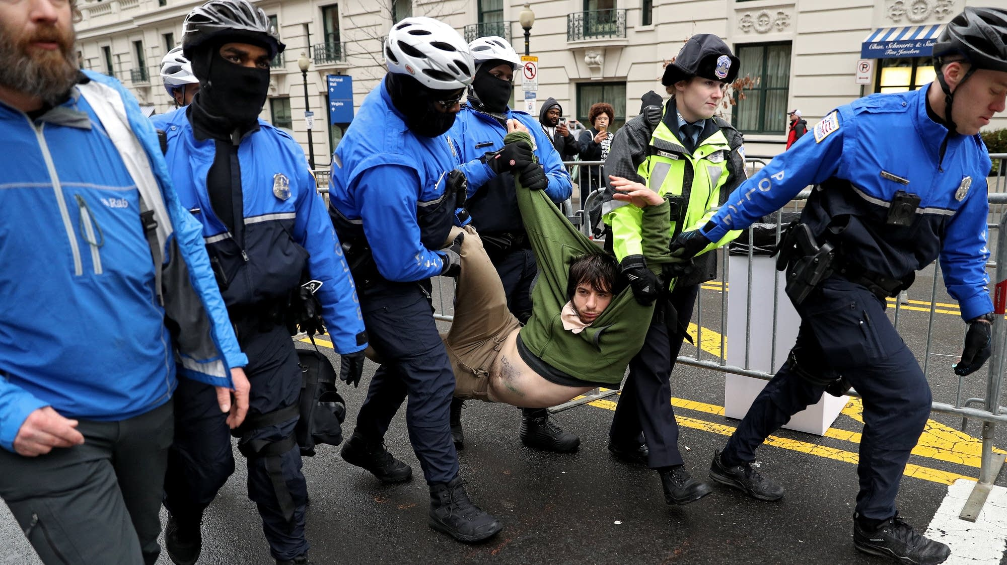 A protester is dragged away from a public access point.