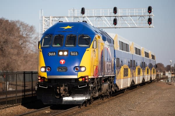 A blue and yellow train approaches a station.