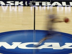 A player runs across the NCAA logo during practice in Pittsburgh