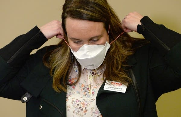 A woman places a mask over her face.