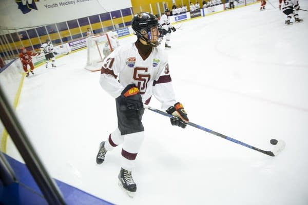A Stoneman Douglas High School hockey player takes the puck up the rink.