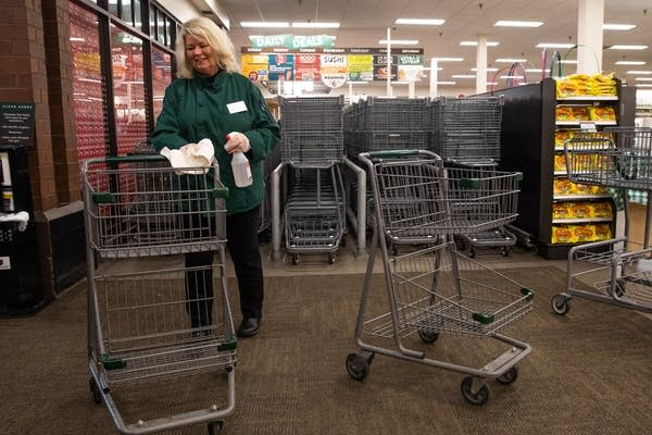 A woman wearing green wipes down a shopping cart.