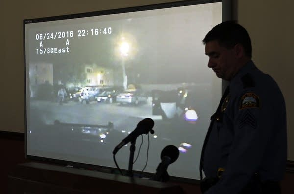 Police Sgt. Mike Ernster in front of squad car video.