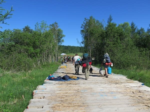 Campers walk across a bridge with their supplies.