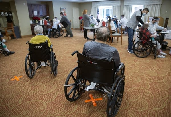 People sit in wheelchairs in a room.