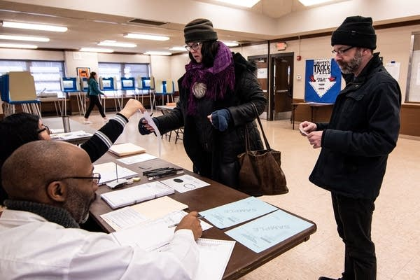 People receive paper ballots.