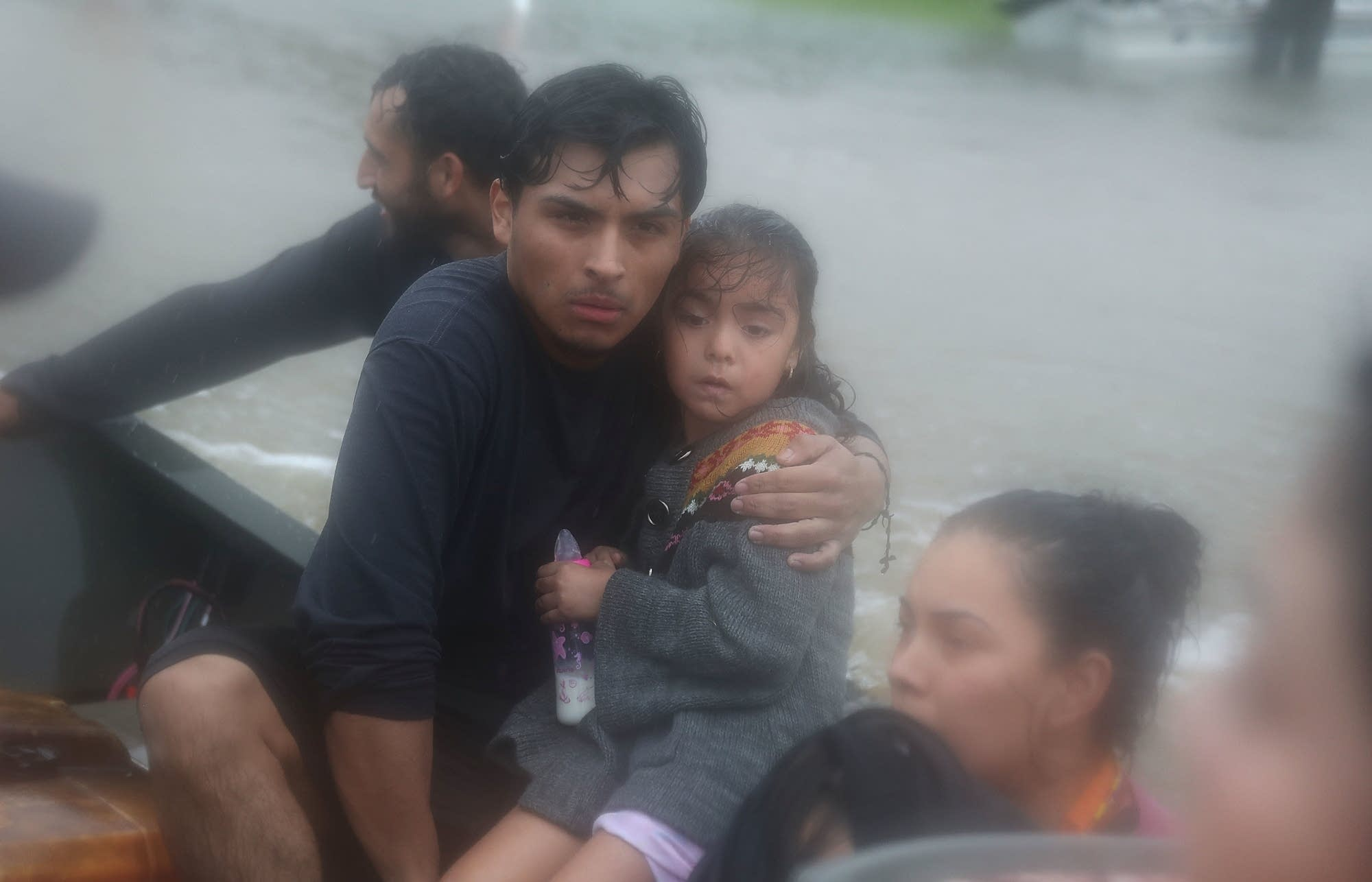 People  evacuate in a boat from their homes.