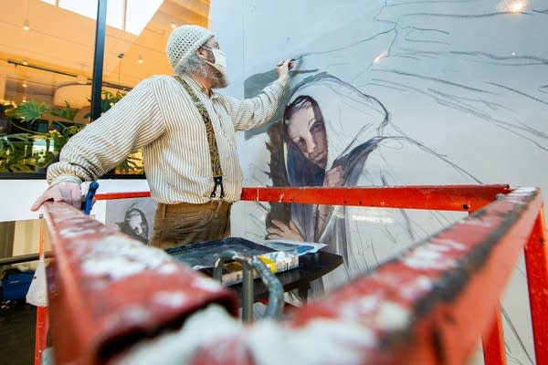 A man works on a painting of a woman on a scissor lift