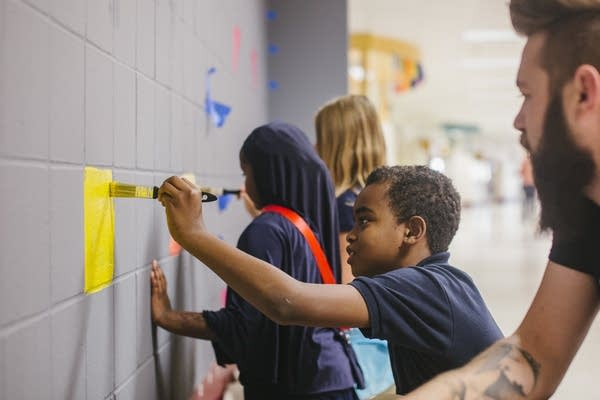 Fourth-grader Jeffrey Willis paints on the mural.