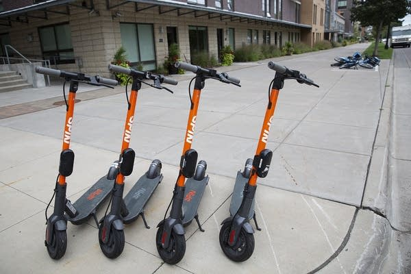 Four orange electric scooters are parked on the sidewalk.