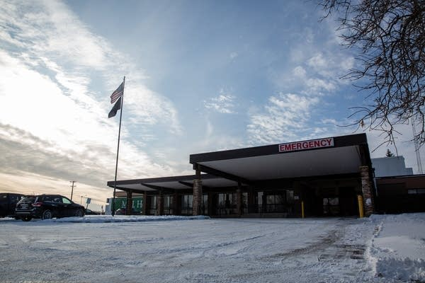 A snowy driveway leads to an emergency room entrance under blue skies