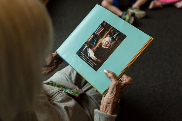 """Ruth Knelman holds a copy of """"The Grandma Book"""" by Todd Parr."""