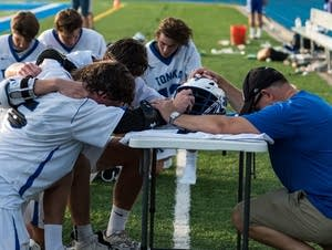 Donald Amorosi, right, kneels with Minnetonka High School lacrosse players.