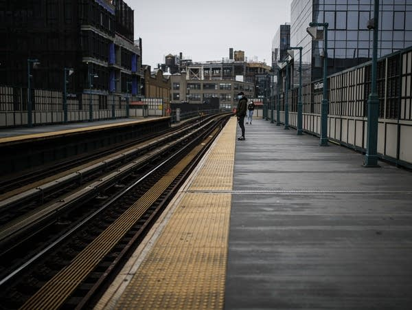 People wearing protective face masks stand on a nearly-empty platform