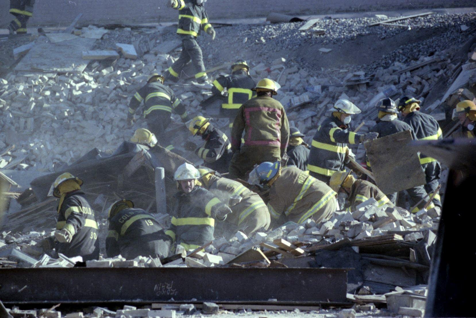 Firefighters comb through the rubble of Bellantti's Pizza & Deli building.