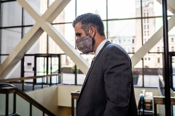 A person wearing a suit and face mask walks in a building.