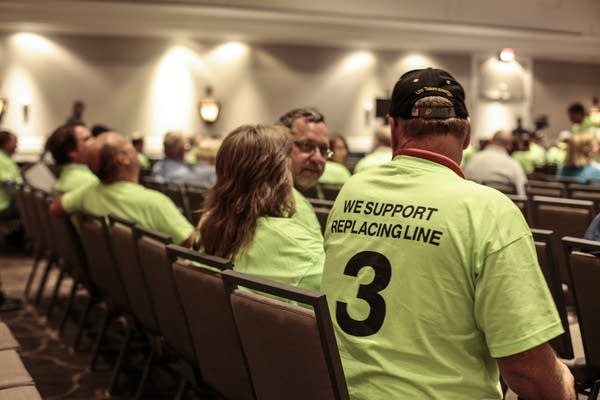 As people join the public hearing they wear green shirts in support.