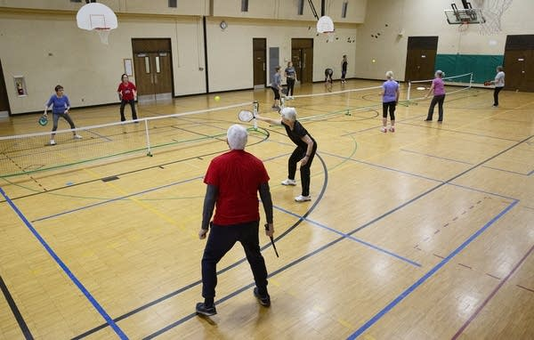 Three groups of people play pickleball on three courts in a gym.