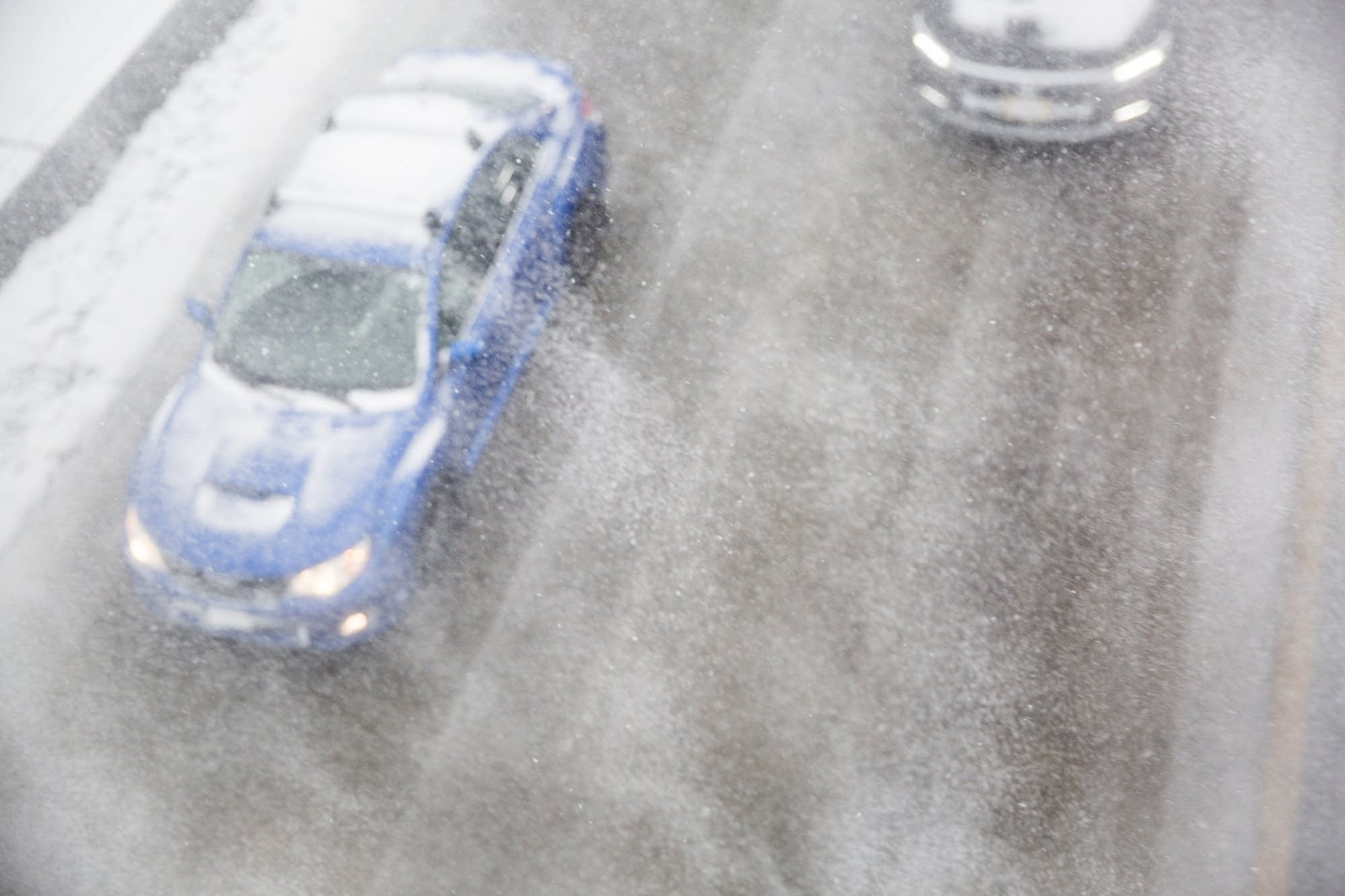 Cars cut through blowing snow on highway 35W