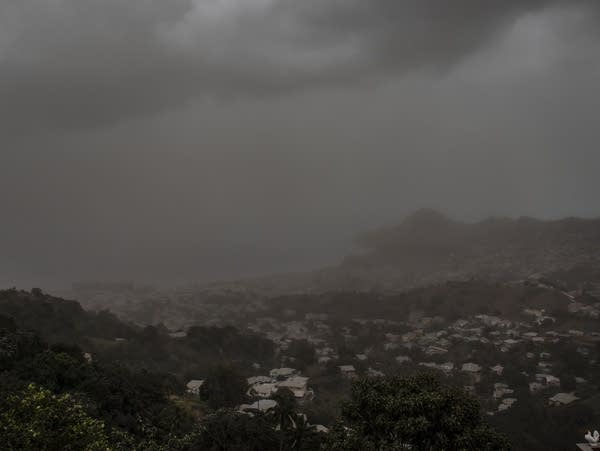 A cloud of volcanic ash hovers over a city