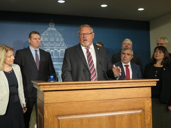 A man at a podium surrounded by colleagues