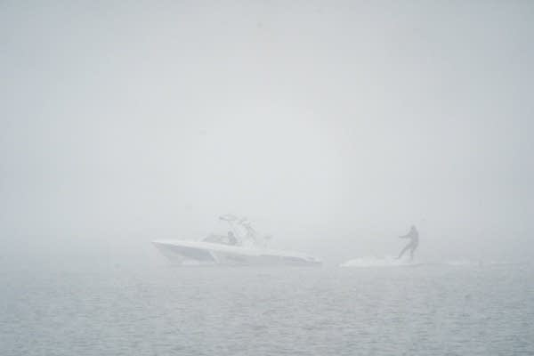 A person surfs behind a boat in the snow.