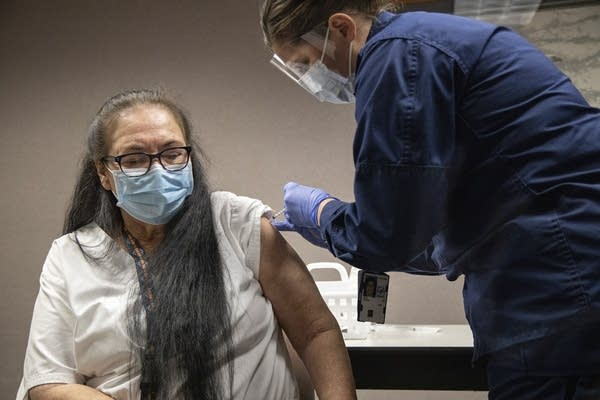 A woman wearing a face mask receives a vaccine.
