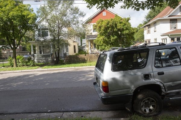A car is parked along the street in a neighborhood.