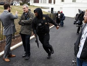 A Secret Service officer rushes past reporters.