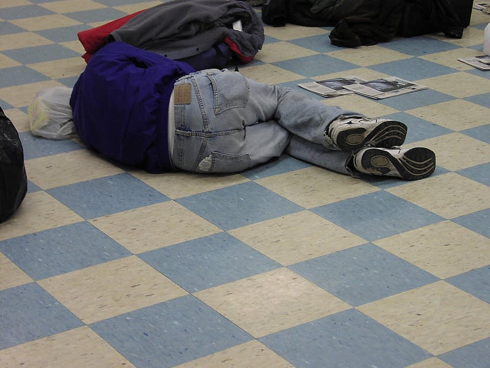 A man rests on the floor at Secure Waiting Space