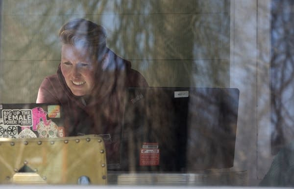 A woman is seen through a window as she works on a laptop.