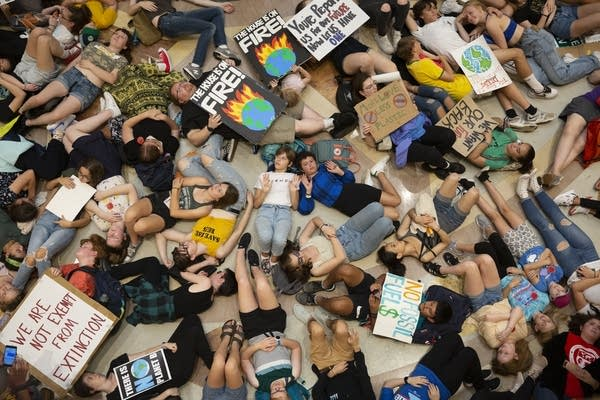 A group of protestors lie on the floor of a rotunda.