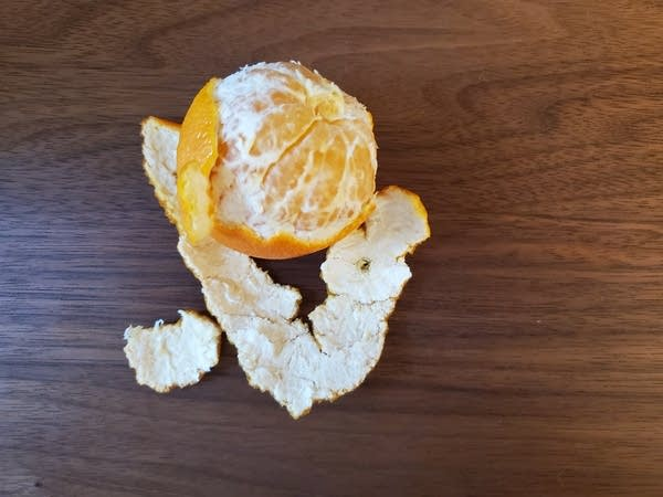 A half-peeled Clementine orange sitting on a wooden desk