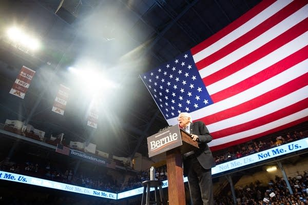 A man speaks in front of a large American flag.