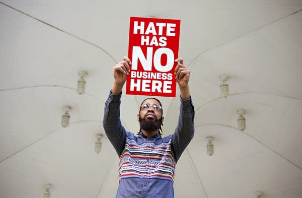"Organizer, activist Wess Philome holds a sign, ""Hate has no business here"""