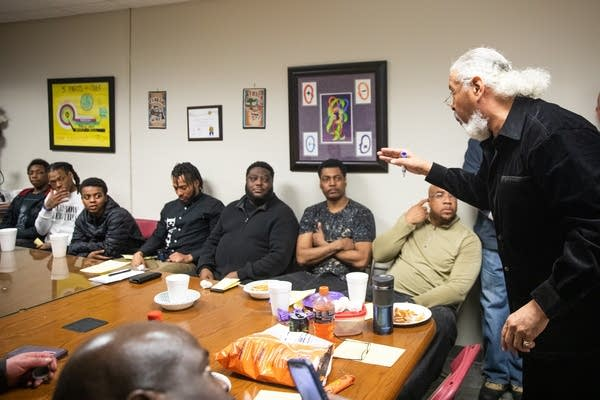 A man with white hair speaks to a room of men.