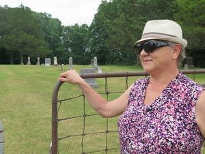 Janet Klug, niece of Elmer Kerestes, stands at the gate of the cemetery.
