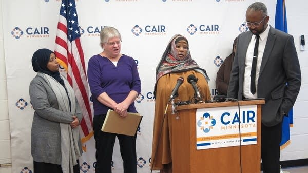 Three women and one man stand near a podium at a press conference.