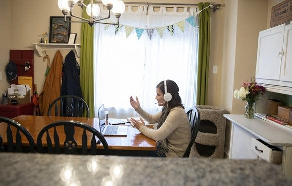 A woman gestures as she sits in front of a laptop at a kitchen table.