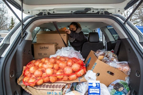 A woman sorts food in the back of an SUV.