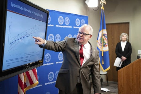A man pointing to a graph on a screen.