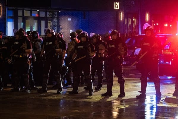 Police in riot gear stand in a line.