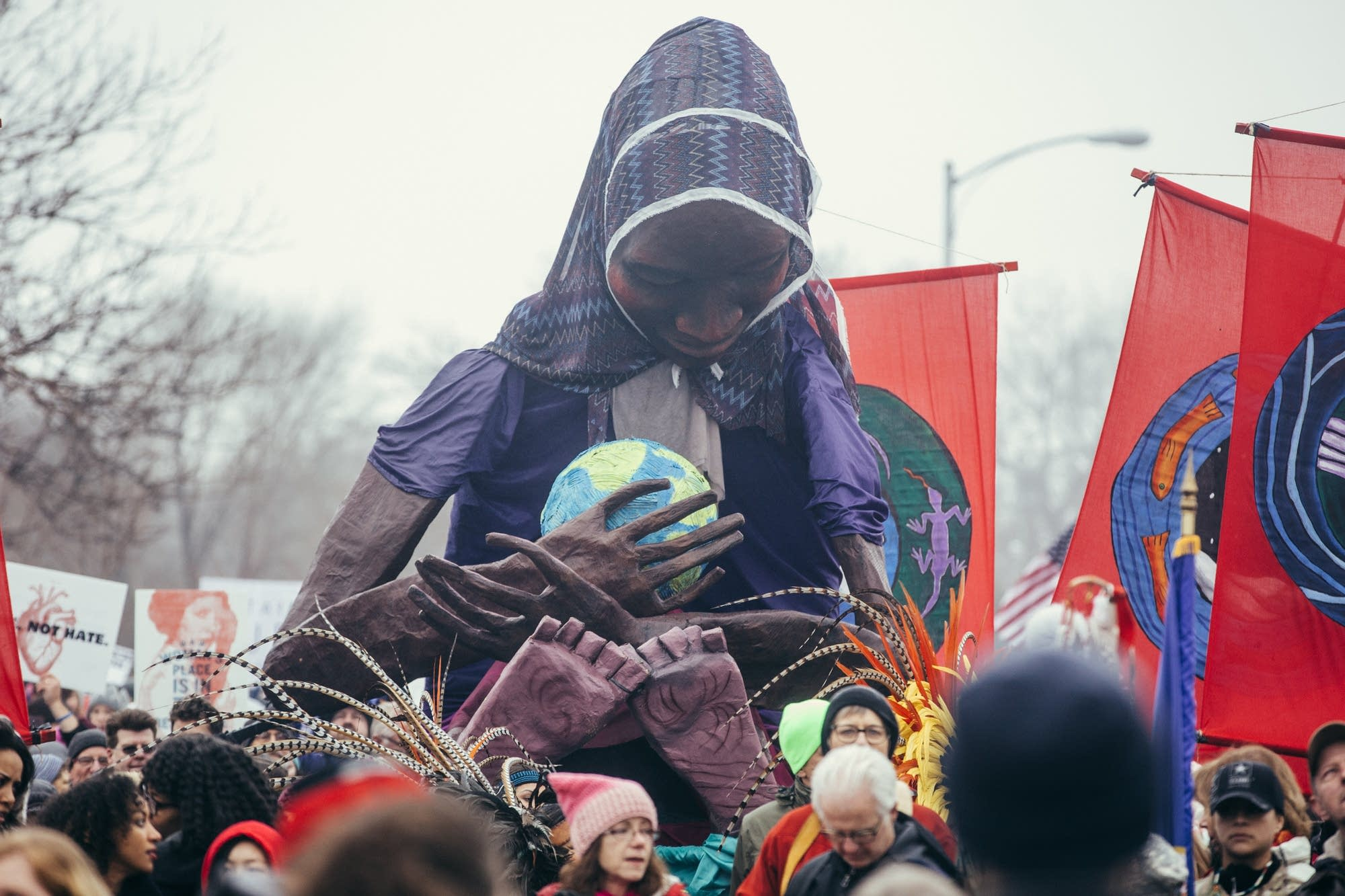 A giant woman holding earth is carried.
